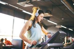 Schöne junge Frau mit dem langen Haar bildet in der Turnhalle auf einer Tretmühle aus Hört Musik in den großen Kopfhörern Auf sei lizenzfreie stockbilder