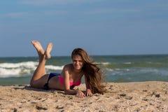 Schöne junge Frau mit dem langen Haar im Badeanzug wirft auf dem Strand nahe dem Meer auf Lizenzfreie Stockbilder