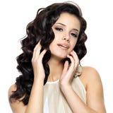 Schöne junge Frau mit dem langen lockigen Haar der Schönheit. Stockbild