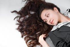 Schöne junge Frau mit dem lockigen braunen Haarlegen Lizenzfreie Stockfotografie
