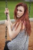 Junge Frau mit dem schönen goldbraunen Haar auf einem Schwingen lizenzfreie stockfotos