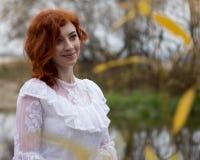 Schöne junge Frau mit dem roten Haar draußen lächelnd im Herbst Lizenzfreies Stockfoto