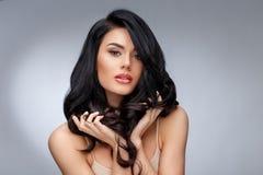 Schöne junge Frau mit dem sauberen gesunden gelockten Haar stockbild
