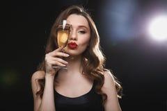 Schöne junge Frau mit den roten Lippen und Glas Champagner Stockbilder