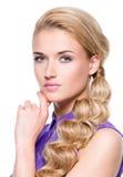 Schöne junge Frau mit der Hand nahe Gesicht Lizenzfreies Stockfoto