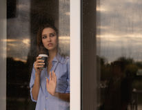 Schöne junge Frau mit der Kaffeetasse, die durch das Fenster schaut Lizenzfreie Stockfotos