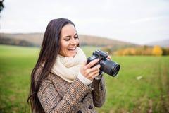 Schöne junge Frau mit der Kamera, die Fotos macht Lange Schatten und blauer Himmel Lizenzfreie Stockfotografie