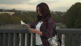 Schöne junge Frau mit der touristischen Karte, die herum in der Stadtstraße schaut stock video