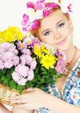 Schöne junge Frau mit einem Blumenkorb lizenzfreie stockbilder
