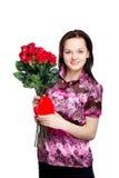 Schöne junge Frau mit einem Blumenstrauß von roten Rosen stockfotografie