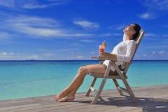 Schöne junge Frau mit einem Getränk durch das Meer Stockfoto