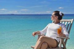 Schöne junge Frau mit einem Getränk durch das Meer Stockbild