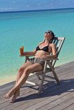 Schöne junge Frau mit einem Getränk durch das Meer Stockbilder