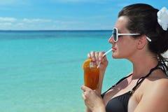 Schöne junge Frau mit einem Getränk durch das Meer Lizenzfreies Stockbild