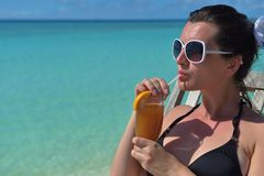 Schöne junge Frau mit einem Getränk durch das Meer Lizenzfreie Stockfotografie