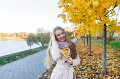 Schöne junge Frau mit einem Lächeln mit einem gelben Blatt des Herbstes im Stadtpark lizenzfreie stockbilder