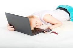 Schöne junge Frau mit einem Laptop und einem Telefon liegt auf warmem Plaid Lizenzfreie Stockfotografie
