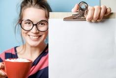Schöne junge Frau mit mit einem leeren Blatt und einem roten Becher auf a Stockbild