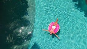 Schöne junge Frau mit einem rosa Laptop auf einem aufblasbaren Ring im Wasser im Swimmingpool Freiberuflich tätig sein, Geschäft stockfoto