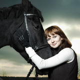 Schöne junge Frau mit einem schwarzen Pferd Lizenzfreie Stockfotografie