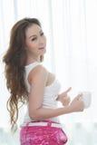 Schöne junge Frau mit einem Tasse Kaffee am Schlafzimmer lizenzfreies stockbild
