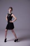 Schöne junge Frau mit elegantem schwarzem Kleid stockbilder