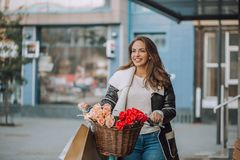 Schöne junge Frau mit Fahrrad und Einkaufstaschen lizenzfreie stockfotos