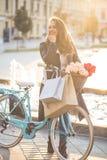 Schöne junge Frau mit Fahrrad und Einkaufstaschen lizenzfreies stockbild