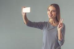 Schöne junge Frau mit Gerät stockfotografie