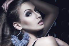 Schöne junge Frau mit grauen Ohrringen Stockfoto