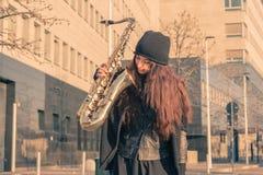 Schöne junge Frau mit ihrem Saxophon Stockbilder