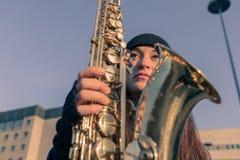 Schöne junge Frau mit ihrem Saxophon Stockbild