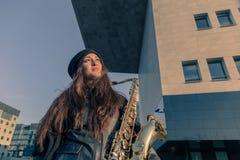 Schöne junge Frau mit ihrem Saxophon Stockfoto