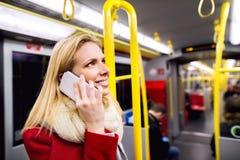 Schöne junge Frau mit intelligentem Telefon in der Untergrundbahn Stockbilder