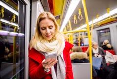 Schöne junge Frau mit intelligentem Telefon in der Untergrundbahn Stockbild
