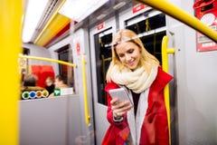 Schöne junge Frau mit intelligentem Telefon in der Untergrundbahn Lizenzfreies Stockbild