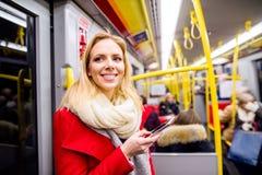 Schöne junge Frau mit intelligentem Telefon in der Untergrundbahn Lizenzfreie Stockfotos
