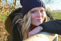 Schöne junge Frau mit Kappenmagerem auf Holz von der Seite Stockbild