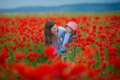 Schöne junge Frau mit Kindermädchen auf dem Mohnblumengebiet glückliche Familie, die Spaß in der Natur hat Porträt im Freien in d lizenzfreie stockbilder