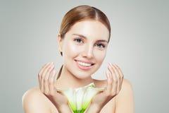 Schöne junge Frau mit klarer Haut und Blumen auf grauem Hintergrund stockbild