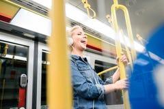 Schöne junge Frau mit Kopfhörern in der Untergrundbahn Stockbilder