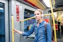 Schöne junge Frau mit Kopfhörern in der Untergrundbahn Lizenzfreie Stockfotos