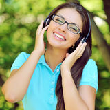 Schöne junge Frau mit Kopfhörern draußen Genießen von Musik Lizenzfreie Stockfotos