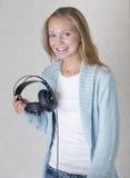 Schöne junge Frau mit Kopfhörern hörend zu lizenzfreie stockfotos