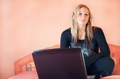 Schöne junge Frau mit Kopfhörern und Laptop stockfotos
