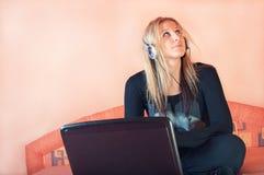 Schöne junge Frau mit Kopfhörern und Laptop lizenzfreies stockbild
