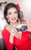 Schöne junge Frau mit kreativem Make-up und der Frisur, die Fotos mit einer Kamera macht Moderner attraktiver Brunette lizenzfreies stockbild