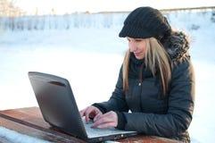 Schöne junge Frau mit Laptop im Winter lizenzfreie stockbilder