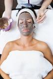 Schöne junge Frau mit Lehmgesichtsmaske im Schönheitsbadekurort detox lizenzfreie stockbilder