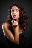 Schöne junge Frau mit Lippenstift stockbild